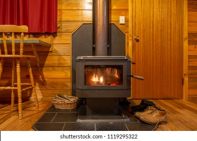 Interior of a warm wooden cottage with burning fireplace and hiking boots placed near the door.