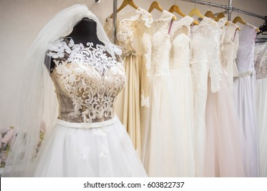 cf96d3e381 Interior of wedding shop. Wedding dress on a mannequin. Assortment of dresses  hanging on