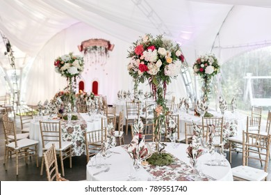 Interior of a wedding tent decoration ready for guests. Served round banquet table outdoor in marquee decorated flowers and silk. Catering concept