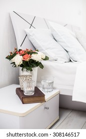 Interior of white bedroom, new linens on the bed, cozy home. Bedside table decor and pillows closeup.