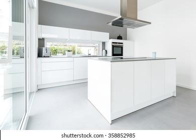 Interior of white kitchen with big windows