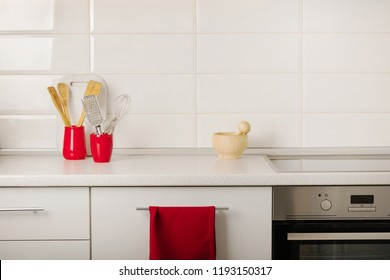 Interior white kitchen with kitchen tools and red crockery. Selective focus.