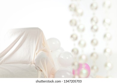 Interior with white and pink balloons and sofa. On the right blurry transparent pearls.