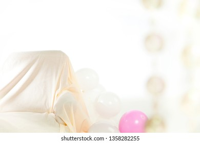Interior with white and pink balloons and sofa. On the right blurry transparent pearls.Background with space for text or logo. Concept of party.