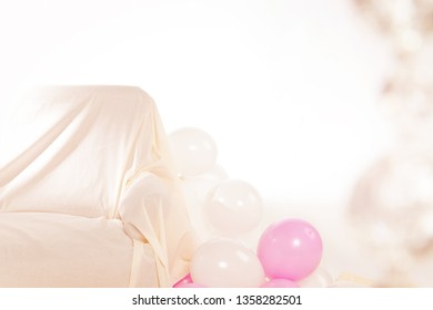 Interior with white and pink balloons and sofa. On the right blurry transparent pearls.Background with space for text or logo. Concept of party. Warm color