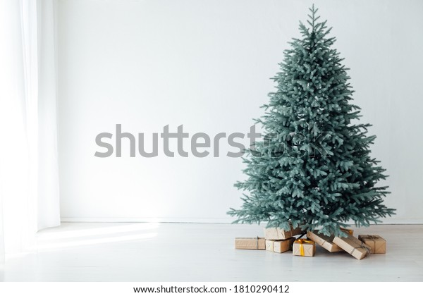 The interior of the white room with a blue Christmas tree with gifts for the new year decor winter postcard