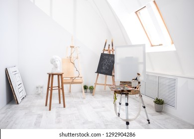 Interior of white studio of the artist, creative person. Easel, brushes, plaster head and figures. Attic, high ceilings. Daylight.