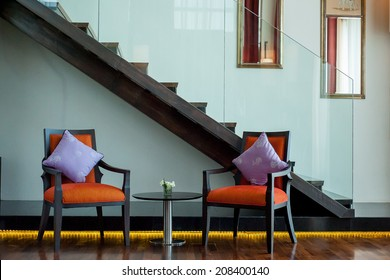 Interior white wall with wooden stairs and 2 chairs