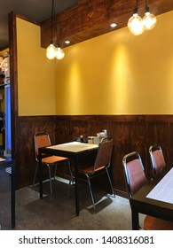 The interior of wooden chairs, tables and yellow walls