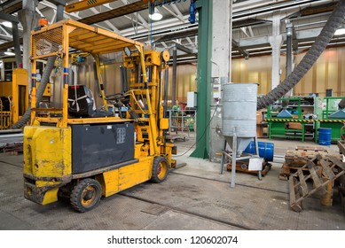 interior of workshop with yellow forklift and tools
