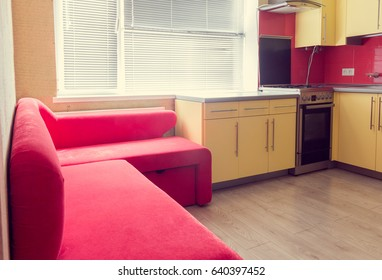 interior of the yellow kitchen with cupboards, window, laminate and red soft couch