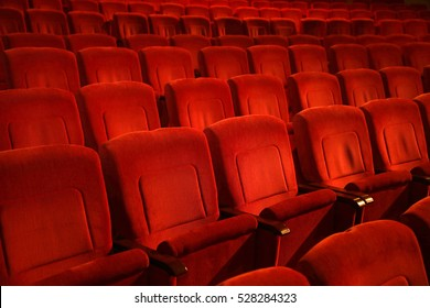 Interiors empty reddish cinema chairs seats in low-key indoors
