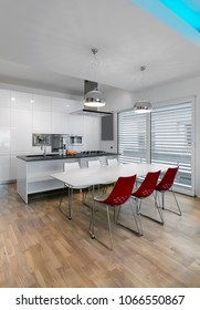 interiors hsots of a modern kitchen in the foreground the white dining table and  red chairs the floor is made of wood