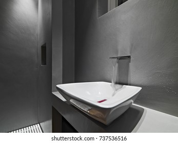 interiors shots of a contemporary bathroom in the foreground the counter top washbasin and the tap