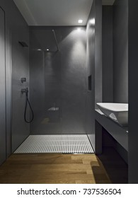 interiors shots of a contemporary bathroom with wooden floor in the bottom the masonry shower glass box with resin walls