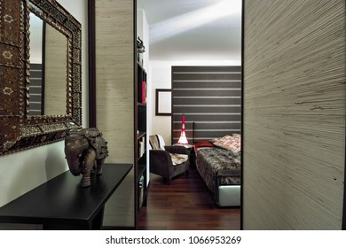 interiors shots of a ethnic bedroom in the foreground the sculpture of a elephant on the background the bed