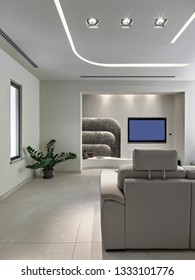 interiors shots of a modern apartment, in the foreground the leather sofa in the background the led television