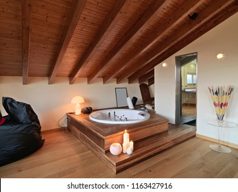 interiors shots of a modern bathroom in the attic room in the foreground the wirlpool bathtub on the two wooden steps instead the floor and the ceiling are made of wood