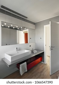 interiors shots of a modern bathroom in the foreground the counter top washbasin and the red furniture