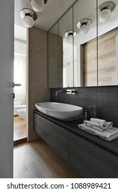 interiors shots of  a modern bathroom in the foreground the counter top washbasin on the wooden furniture the floor is made of wood
