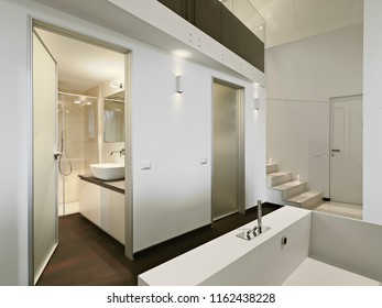 interiors shots of a modern bathroom in the foreground the bathtub instead the washbasin and the shower cubicle in the background are behind the glass door