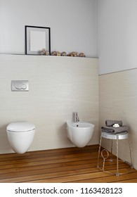 interiors shots of a modern bathroom in the foreground the bidet and toilet bowl the floor is made of wood