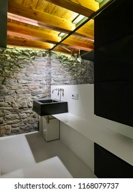 interiors shots of a modern bathroom in the foreground the toilet bowl and the bidet on the background the column washbasin and the big mirror the wall is of stone