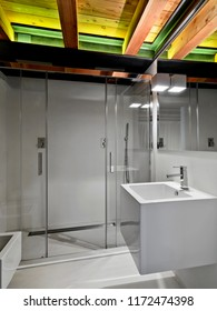 interiors shots of a modern bathroom in the foreground teh wall mounted washbasin in the background the glass shower cubicle