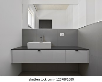 interiors shots of a modern bathroom in the foreground the counter top washbasin and the big mirror