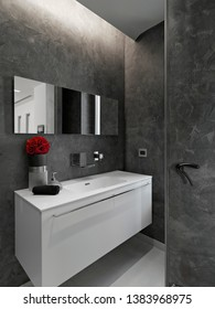 interiors shots of a modern bathroom in the foreground the white lacquered washbasin cabinetwith big mirror
