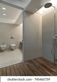 interiors shots of a modern bathroom in the foreground the masonry shower cubicle with wooden floor in the bottom the bidet and toilet bowl