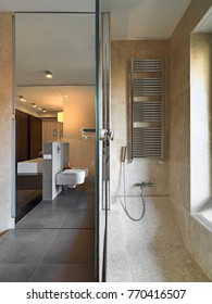 interiors shots of a modern bathroom in the foreground the bathtub and shower cubicle coated with mosaic tiles  in the bottom the washbasin