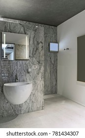 interiors shots of a modern bathroom in the foreground the wall-mounted washbasin the walls are coating of marble and the floor is made of concrete