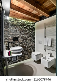 interiors shots a modern bathroom with stone wall and wooden ceiling the floor is made of resin