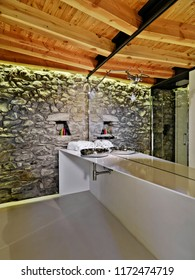 interiors shots of a modern bathroom whose floor is made of resin and the ceiling made of wood