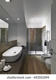 interiors shots of a modern bathroom whose floor is made of wood  in foreground the counter top washbasin on the wood furniture in the bottom the masonry shower cubicle with glass door