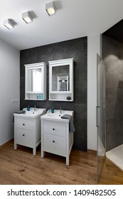 interiors shots of a modern bathroom with wooden floor in the foreground two washbasins cabinets