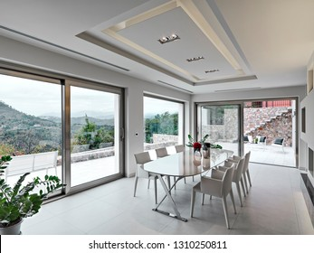 interiors shots of a modern dining room in the foreground the dining table and its chairs overlooking on the exterior terrace