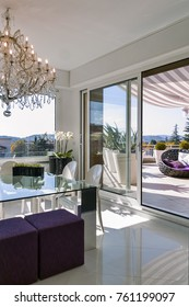 interiors shots of a modern dining room with glass dining table and two purple hassock overlooking on the terrace