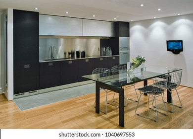 interiors shots of a modern kitchen in the foreground the glass dining table and iron chairs the floor is made of wood