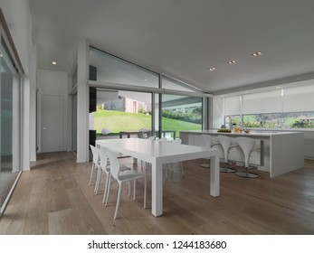 interiors shots of a modern kitchen in the foreground the white dining table on the background the kitchen island the floor is made of wood
