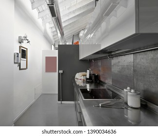 interiors shots of a modern kitchen in the foreground the electric induction cookers the floor is made of concrete