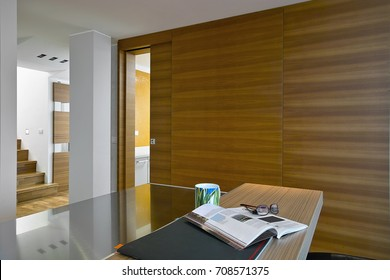 interiors shots of a modern kitchen in the foreground the kitchen island and the wall covered of wainscoting in the background the wooden staircase