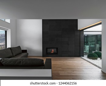 interiors shots of a modern living room in the foreground the leather sofa and the fireplace the floor is made of wood