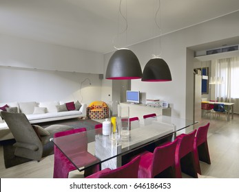 interiors shots of a modern living room in foreground of glass dining table overlooking on the fabric sofas and the kitchen