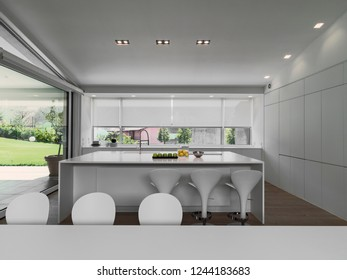interiors shots of a modern white kitchen with kitchen island the floor is made of wood