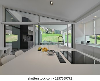 interiors shots of a modern white kitchen island in the villa with induction cooker and integrated sink overlooking on the garden