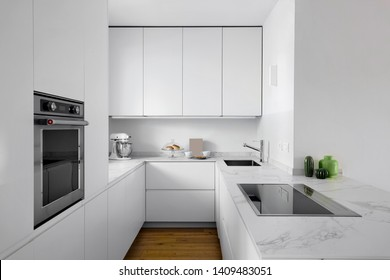 interiors shots of a modern white lacquered kitchen with wooden floor