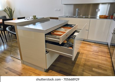 interiors shots of a modern white lacquered kitchen with kitchen island whose drawers are opened the floor is made of hardwood