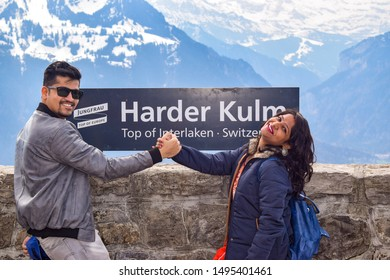 Interlaken, Switzerland, 2019: Indian Couple in woolen wear Posing in front of Harder Kulm Sign Board in different poses. The said location is a famous tourist destination in Switzerland